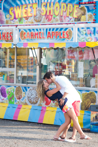 Couple kissing in front of Sweet Shoppe at fair