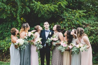 Bridesmaids blowing kisses to groom who is looking up at the sky,