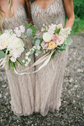 36 bridesmaids wearing taupre dreses with beads holding loose floral bouquets