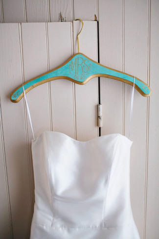 strapless wedding dress hanging from blue monogrammed hanger