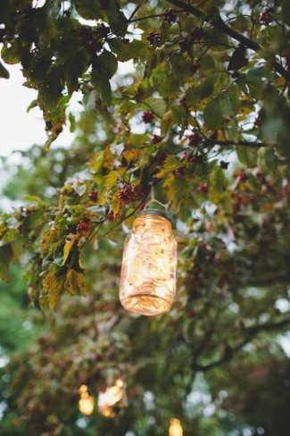 mason jar lantern hanging from a tree lite up