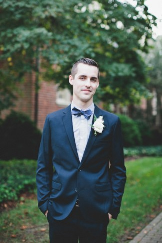groom wearing blue suit with blue bow tie and bouttoniere