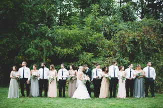 Brdie and groom standing with heads together while their bridal party line up on each side