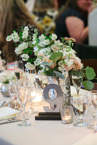 Silver table number at rustic wedding reception with mercury glass vases and candle holders