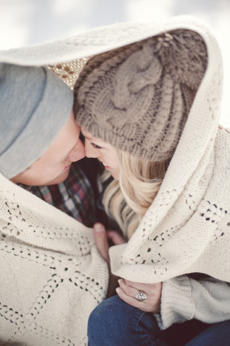 5 engaged couple wearing beanies sitting in the snow under a blanket