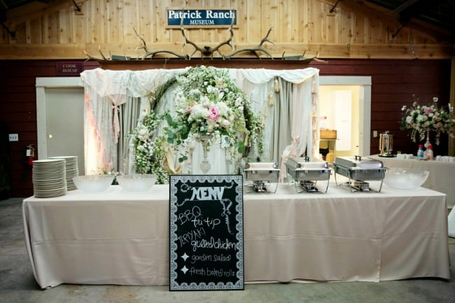 Rustic Wedding reception buffet table with loose floral arrangement and chalkboard sign