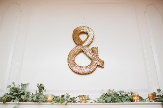 gold sparkly ampersand sign over a mantal