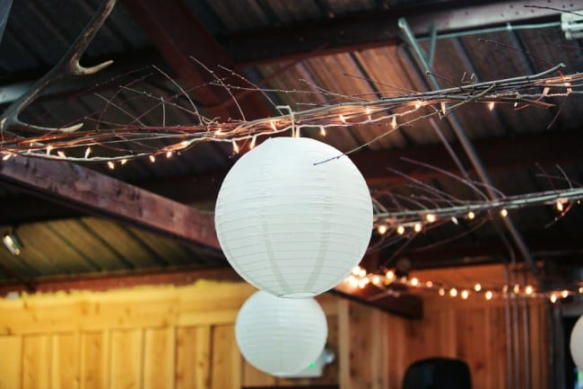 lanterns hanging from the ceiling with white lights and twigs