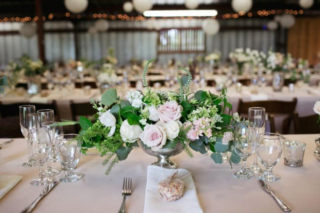 Rustic wedding reception with loose floral arrangement in a mercury vase and bird seed favors