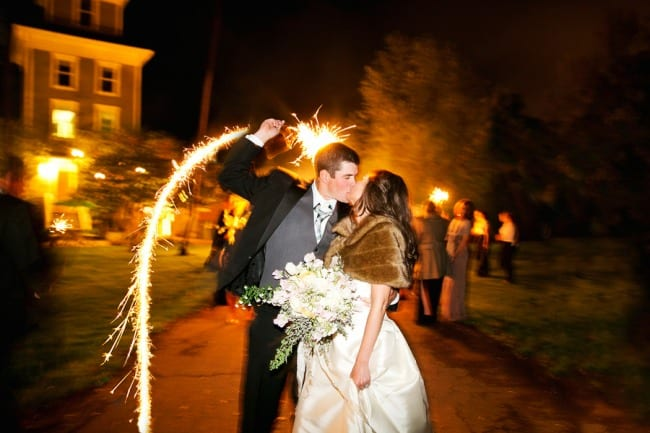bride and groom kissing outside with a sparkler