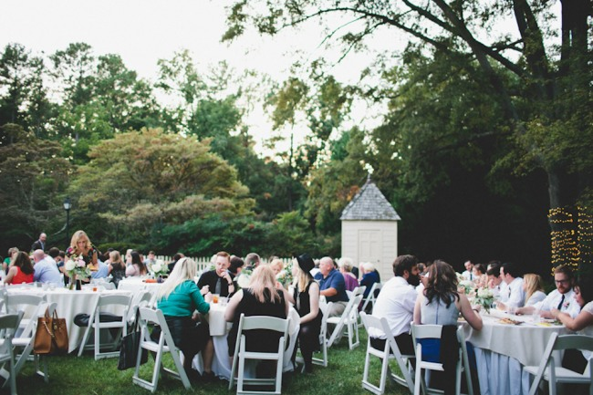 Outdoor wedding reception on lawn with white fold up chairs and round tables