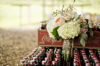 green white and blush bridal bouquet in a pile of coke-a-cola bottles
