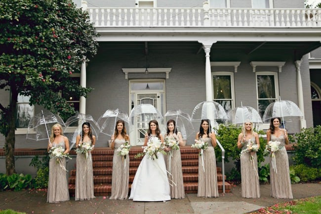 Bride with bridesmaids standing in a line holding clear umbrellas at PATRICK RANCH MUSEUM
