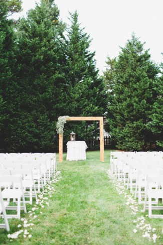 Outdoor wedding ceremony in the gradd with white chairs