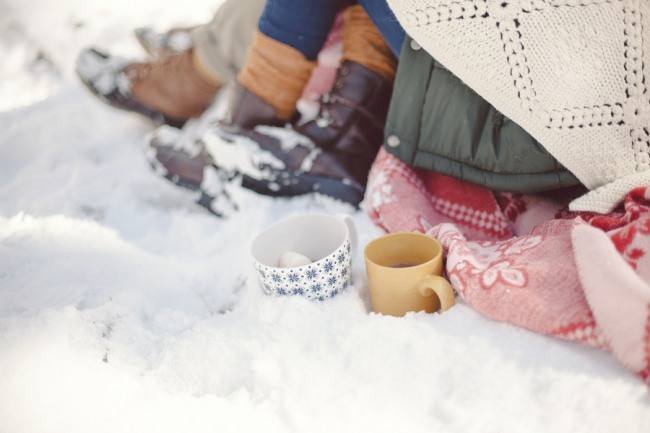 An engaged couple snuggling on a blanket in the snow with 2 mugs of hot chocolate