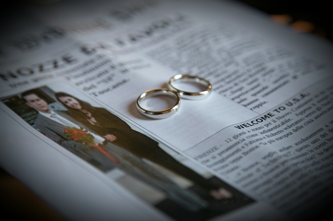 Bride and groom DIY Newspaper about their wedding day with two gold rings on top