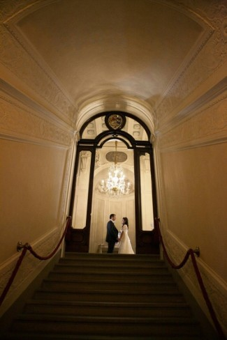 Bride and groom at the top of stairwell under a chandaliere at four season hotel in florence