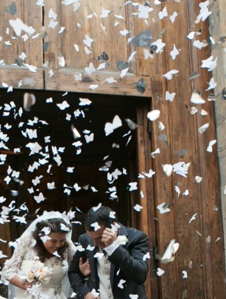 Bride and groom covering as paper confetti fall from the sky