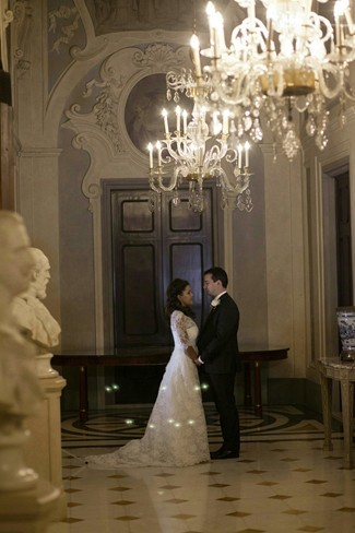 Bride and groom standing under chandaliere at the four season hotel in florence