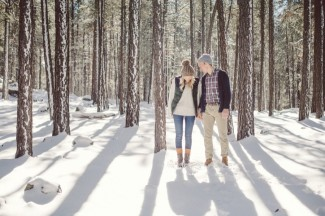 Couple walking in the forest together with snow on the ground