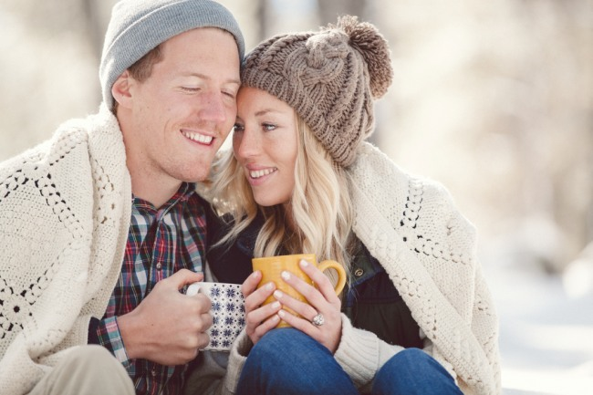 Engaged couple drinking hot chocolate with a blaket around them sitting in the forest