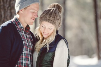 Engaged couple standing together in the forest wearing beanies and black vests