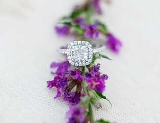 cushion cut engagement ring around purple flowers