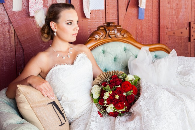 Bride laying on a vintage sofa holding red flower bouquet