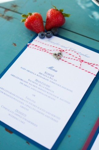 white wedding invitation with blue background and red and white string with heart charm attached