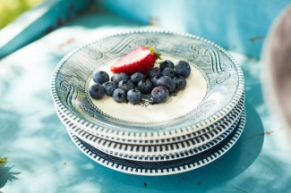 stack of blue pattern china plates with blueberries and strawberries