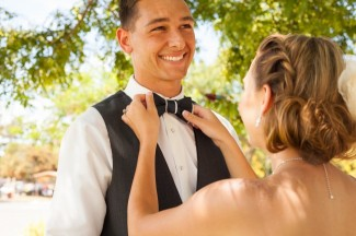bride with hair in a bun straightening grooms bow tie
