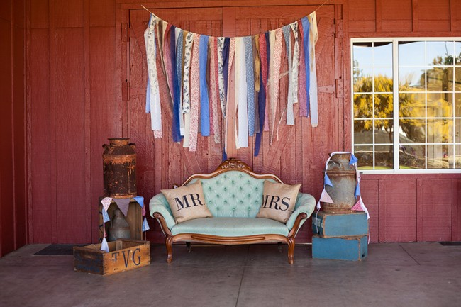 Vintage blue sofa with mr and mrs burlap pillows and vintage milk cans