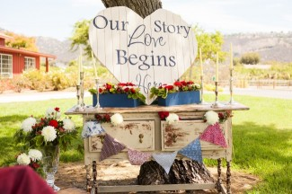 Vintage dresser with a white wooden sign that says our love story begins here, bunting banner and candle sticks