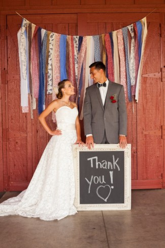 Bride and groom standing together looking at each other with a chalkboard thank you sign