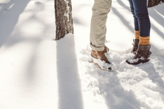 Photo of a couple's feet standing in the forest with snow on the ground