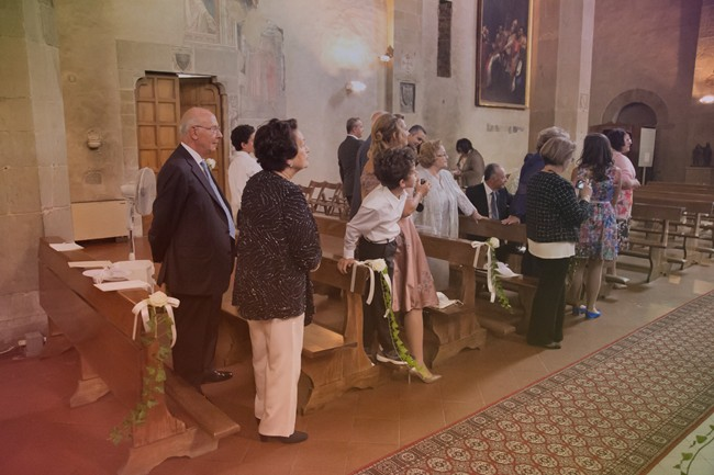 Wedding guests looking down the aisle of church in florence italy to see bride coming