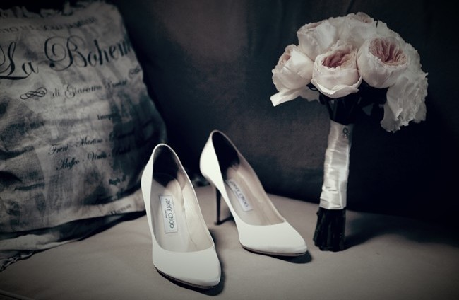 White jimmy choos for bridal shoes beside a pink floral bouquet