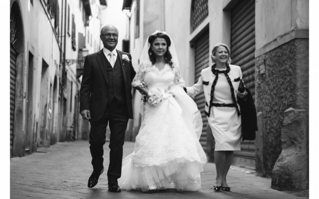 black and white photo of bride and her parents walking through street of florence to church