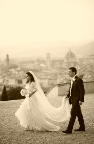 bride and groom walking with florence city scape in the background. Groom holding brides train