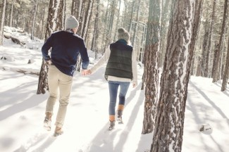 couple walking hand and hand in the snow walking through the forest