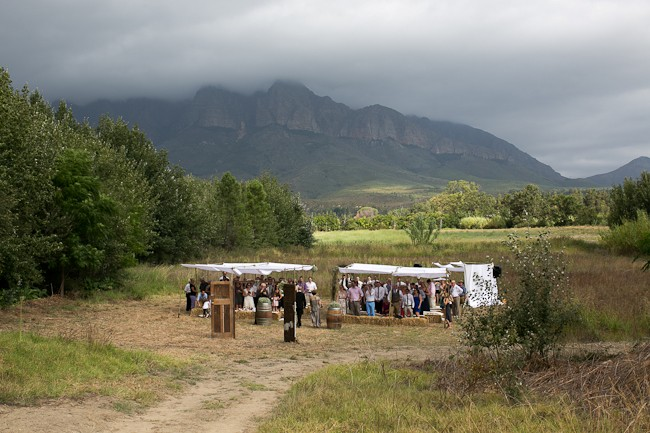 Outdoor wedding ceremony in a field with rainclouds in the mountain backdrop