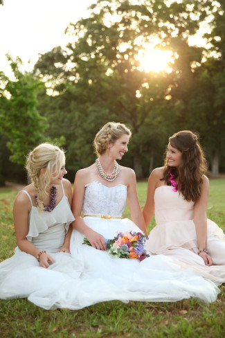bride with two bridesmaids sitting in grass with sun shining behind