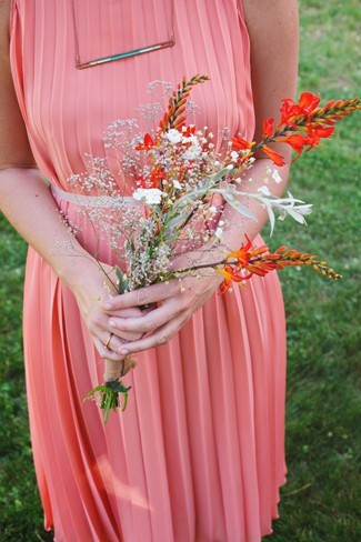 Bridesmaid wearing pink pleated gown holding wild flowers