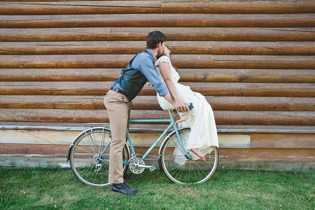 Bride and groom on a bike while kissing with log cabin behind