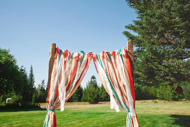 Strands of colorful pink, white, teal material for wedding ceremony arbor