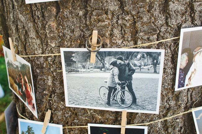 pictures of the bride and groom hung up using clothes pegs and twine around a tree