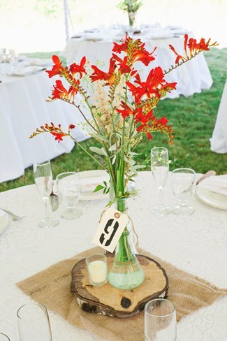 Wedding reception centerpiece using red wild flowers, table number and wood slab
