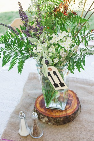 Wedding reception centerpiece using purple and white wild flowers, table number and wood slab