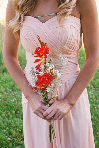 Bridesmaid wearing a strapless peach dress and holding wild flowers