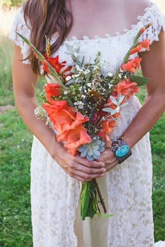 Bride wearing her family wedding dress holding wild flowers